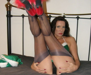 Older woman in Xmas attire poses by the tree in nylons and red mules