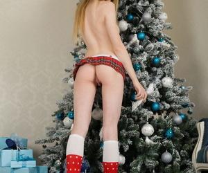 Slim teen Monika takes off bra and panties in Xmas cap afore Christmas tree
