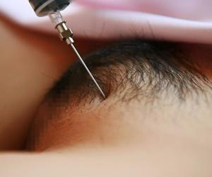 Kinky Japanese nurse Namie Koshino pokes her naked body parts with a needle