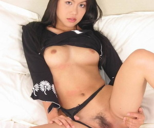 Young Asian girl dildos her trimmed pussy in boots atop her bed