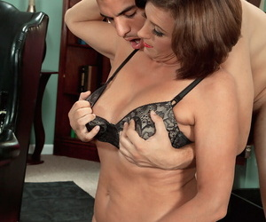 Middle aged woman Yasmine Beale seducing her male patient in her office