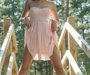 Nice teen Oxana Chic poses her tan lined body on wooden stairs of hiking trail