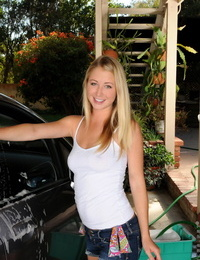 Young blonde girl touts her hot ass while washing a vehicle in carport