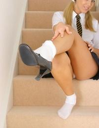 Charming teen Belle works free of her schoolgirl uniform on stairs