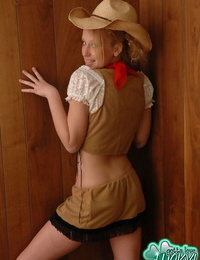 Cute blonde girl with blue eyes flashes her bare ass in cowgirl attire