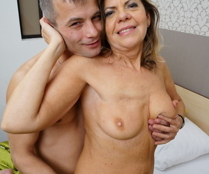 Mature couple undress as they fan the flames before fucking on a bed