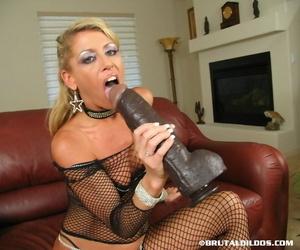 Older blonde rides a massive black dildo after sucking on it in mesh attire