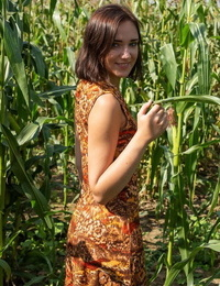 Young brunette Oxana Chic attends to her horny pussy on floor of cornfield