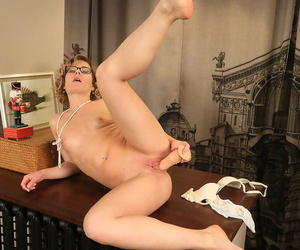 Hot mature Lisa in glasses licks her toy before riding close up on the table