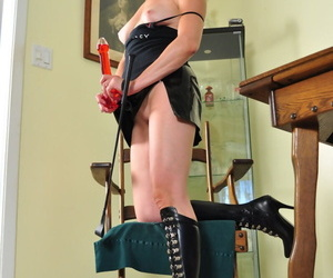 Mature lady in boots Mina Gorey holds a dildo in one hand and a crop in other