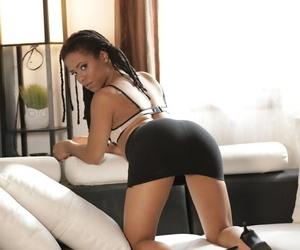 Ebony solo girl Kira Noir shows some leg before removing her office attire
