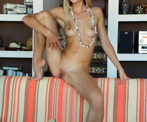 Erotic model Nika N drapes herself over the couch naked & barefoot in beads