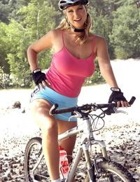 Blonde cyclist Carol G pauses to masturbate underneath a shade tree