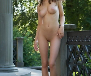 Busty girl with brown hair shows her nice ass while going naked on veranda