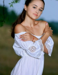 Adorable teen Jennifer Hart slips out of a white dress to pose nude in a field