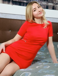 Young blonde Daniella casts aside her red dress to pose naked on her bed