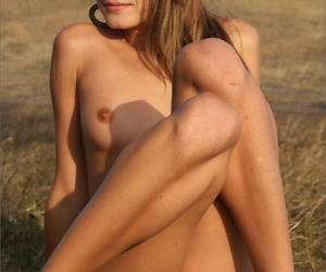 Girl next door type strikes great poses under a tree in a wide open field