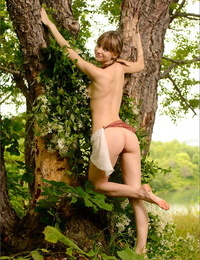 Adorable college aged girl displays her thin body under an old tree