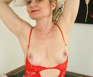 Mature lady Isabella Diana strips to fishnet stockings together with skivvies on bureau