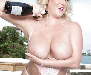 Thick blond woman Holly Wood pouring bubbly over big tits and twat beside pool
