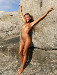 Young solo girl Mango A displays her bald pussy and sexy ass on seaside rocks