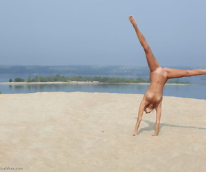 Flexible blonde Afina meditating naked and stretching on the beach