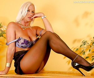 Stunning mature blonde in pantyhose stripping off her dress and lingerie top