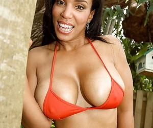 Mature ebony lady Soleil Hughes frees big natural tits from bikini outdoors