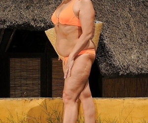 Chubby mature brunette in sunglasses taking off her bikini outdoor