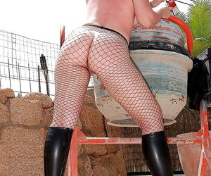 Mature lady in fishnet outfit revealing her goods and caressing herself