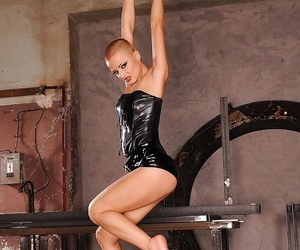 Bald fetish babe with slender legs posing in latex outfit