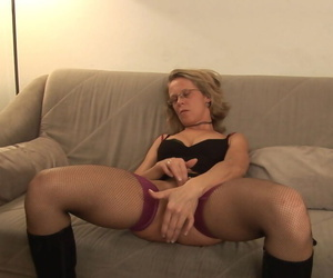 Older woman in glasses and boots pleasures her own pussy on loveseat