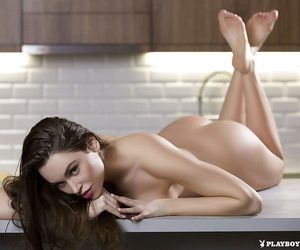 Brunette centerfold Jasmine displaying great legs and nice tits in kitchen