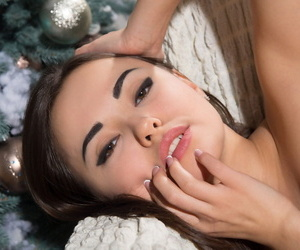 Sweet young brunette Li Moon undresses to pose her hot ass by the Xmas tree