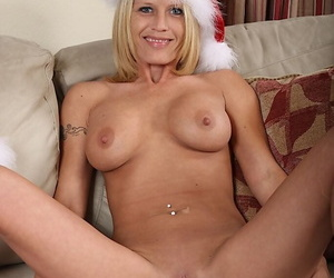 Mature blonde taking off her Christmas outfit and exposing her shaved cunt