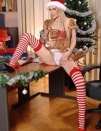 Blonde babe shows off stocking clad legs and ass in Christmas uniform