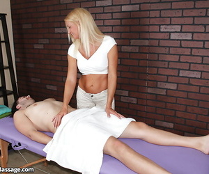 Fully clothed blonde massagist giving a handjob to tattooed man