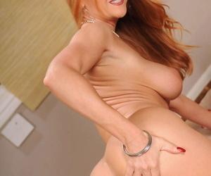 Mature redhead Janet Mason slides a vibrator back her trimmed shrub