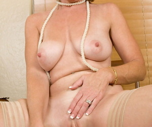 Mature woman Samantha Stone wears a sun hat and nylons while masturbating