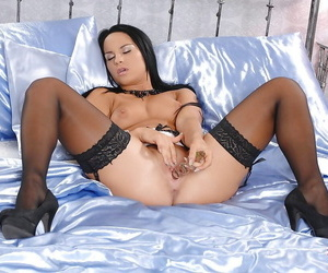 Pretty babe in stockings Bettina DiCapri playing with her glass dildo
