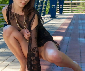 Erotic model Bogdana B squats outside in sheer lace top spreading her legs