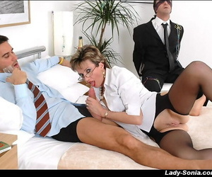 Mature femdom tortures a blindfolded guy and gives a blowjob to another