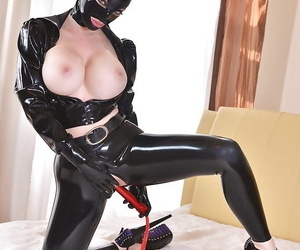 Latex attired female Latex Lucy sucking vibrator before inserting it in twat