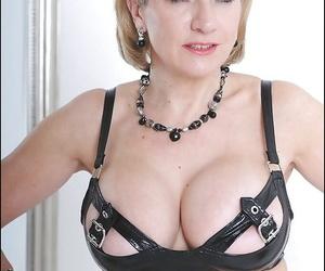 Dazzling adult talisman lady with enhanced Bristols posing alongside latex tool