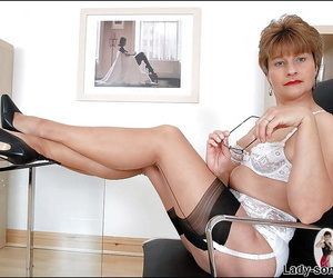 Mature fetish lady in glasses posing in lacy lingerie and stockings