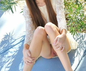 Skinny teen girl gives a naked upskirt view and spreads naked pussy outdoors