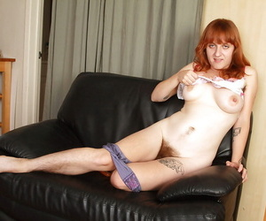 Mature redhead babe Velma caresses her very hairy cunt with comb