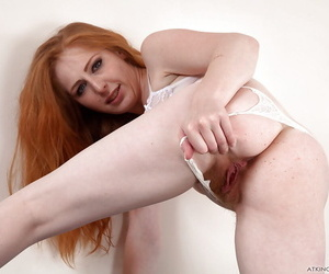 Older redhead Tia Jones stretching hairy ginger pussy wide open on couch