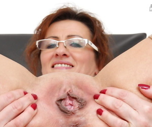 Filthy mature nurse concerning glasses takes off say no to panties and exposes say no to cunt