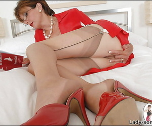 Sexy mature lady in stockings posing on the bed and fingering her twat